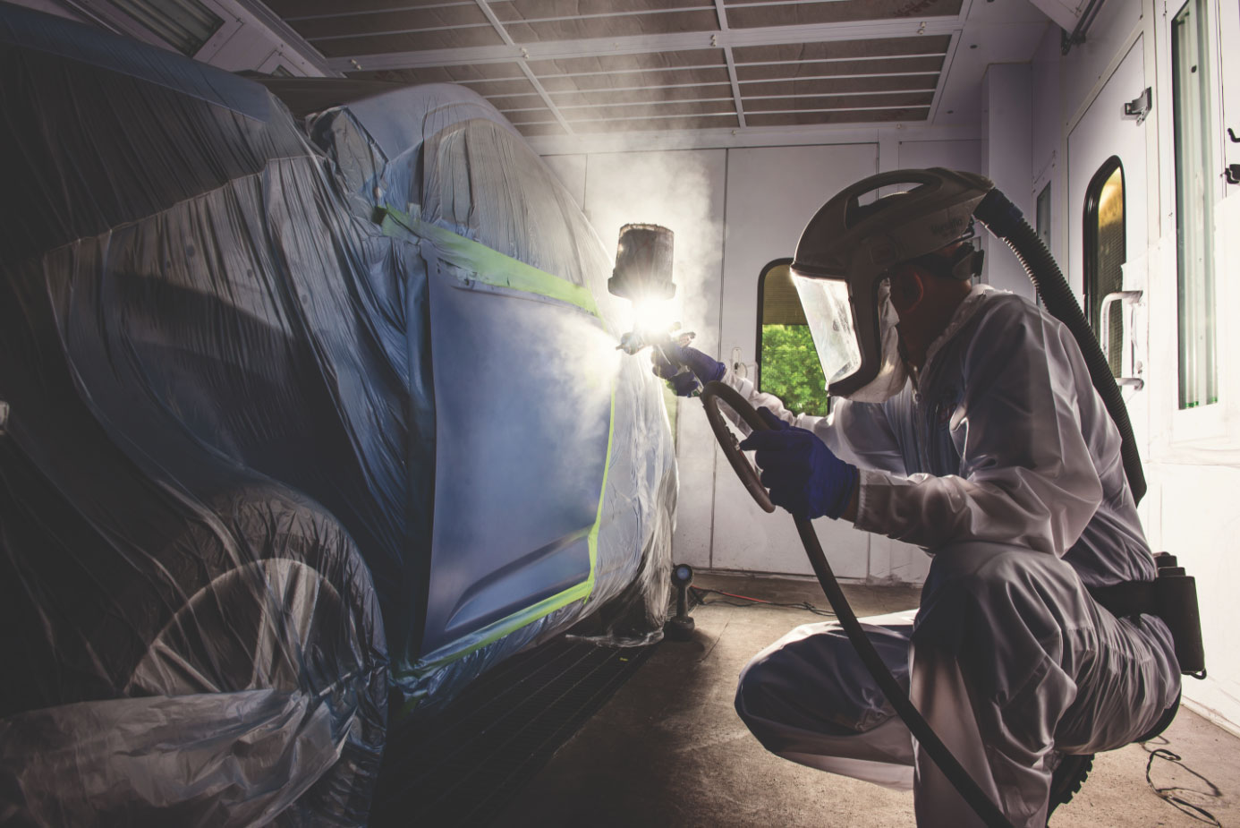 Automobile technican spraying vehicle in paint booth